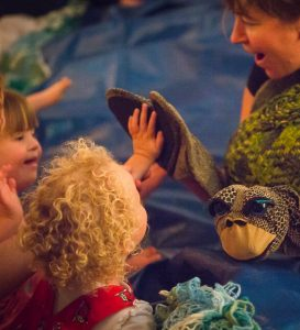 Oddysea - © Jessica Wyld / Actress using turtle puppet to interact with disabled children audience
